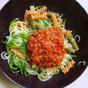 bunte Spiralnudeln und Zucchininudeln mit veganer Sojabolognese auf einem Teller