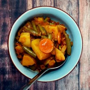 veganes Gulasch mit Kartoffeln, Karotten und grünen Bohnen in einer hellblauen Schüssel angerichtet
