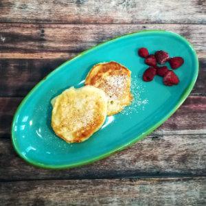 Zwei vegane Pancakes mit Himbeeren auf einem türkisen länglichen Teller