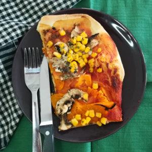 Vegane Pizza mit Tomaten, Pilzen und Mais belegt auf einem Teller mit Messer und Gabel