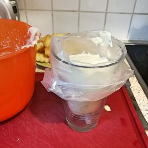 Vegane Vanillecreme in Spritzbeutel, welcher über ein Glas gestülpt ist.