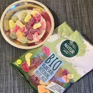 Vegane Saure  Mischung , Frutti Frizzi, von Hofer bzw. Aldi Süd. Verpackung sowie ein Teller mit Fruchtgummis sind abgebildet.