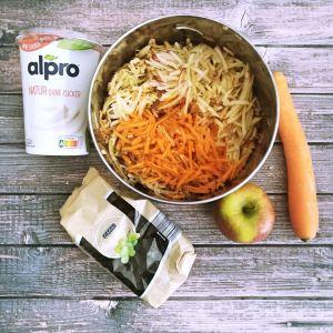 ein Apfel, eine Karotte, Rosinen und Sojajoghurt natur